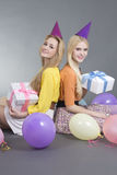 Adolescentes sonrientes que se sientan con los regalos y los globos coloridos Foto de archivo libre de regalías