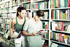 Adolescentes sonrientes que sostienen el libro y que leen junto Imagen de archivo libre de regalías