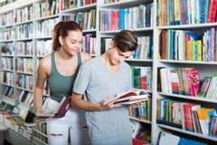 Adolescentes sonrientes que sostienen el libro y que leen junto Foto de archivo