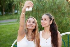 Adolescentes sonrientes que toman la foto del uno mismo con el teléfono móvil Imagen de archivo libre de regalías