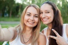 Adolescentes sonrientes que toman la uno mismo-foto al aire libre Foto de archivo
