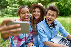Adolescentes sonrientes que toman Selfie en parque Fotografía de archivo