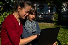 Adolescentes sonrientes que usan el ordenador portátil en el parque Fotos de archivo libres de regalías