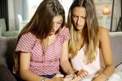 Adolescentes tiranizados en la sentada triste de la red social en el sofá Fotos de archivo libres de regalías