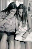 Adolescentes tiranizados en la sentada triste de la red social en el sofá blanco y negro Imágenes de archivo libres de regalías