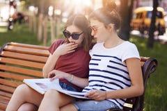 Adolescentes y concepto el estudiar Las hembras hermosas en las sombras de moda, enfocadas en el libro, se sientan en banco, tien Foto de archivo libre de regalías