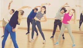 Adolescentes y muchachas con el instructor que estira en pasillo de danza Fotos de archivo