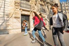 Adolescentes y muchachas rollerblading en la ciudad Imagen de archivo libre de regalías