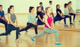 Adolescentes y muchachas sonrientes que aprenden en pasillo de danza Fotografía de archivo