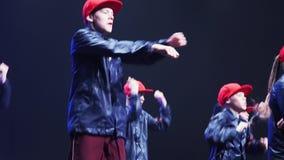 Adolescentes y muchachos agradables en trajes oscuros con de los casquillos danza roja sincrónicamente almacen de video