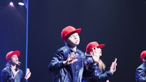 Adolescentes y muchachos lindos en trajes oscuros con de los casquillos danza roja sincrónicamente almacen de video