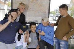 ADOLESCENTES Y SMARTPHONE IPHONES DE DENMARK_DANISH Foto de archivo libre de regalías