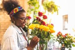 Adolescenti afroamericani che odorano Rose Flowers gialla immagine stock libera da diritti