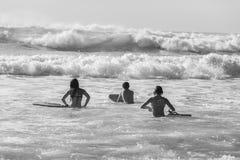 Adolescenti che nuotano le onde praticanti il surfing fotografia stock