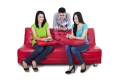 Adolescenti che per mezzo del telefono cellulare Immagine Stock