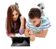 Adolescenti che per mezzo di una compressa Fotografie Stock