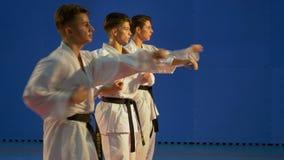 Adolescenti che praticano addestramento di perforazione di karatè per il kata archivi video