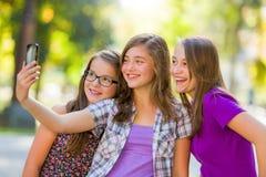 Adolescenti che prendono selfie in parco Immagini Stock Libere da Diritti