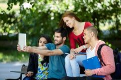 Adolescenti che si siedono su un banco che prende selfie e andar in giroe Immagine Stock Libera da Diritti