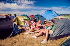 Adolescenti che si siedono sulla terra davanti alle tende Immagini Stock