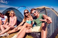 Adolescenti che si siedono sulla terra davanti alle tende Fotografia Stock Libera da Diritti