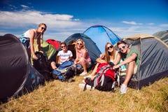 Adolescenti che si siedono sulla terra davanti alle tende Fotografie Stock Libere da Diritti