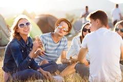 Adolescenti che si siedono sulla terra davanti alle tende, mangianti Immagini Stock Libere da Diritti