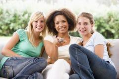 Adolescenti che si siedono sullo strato fotografia stock