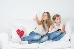 Adolescenti che si siedono sullo strato con il telefono Fotografia Stock