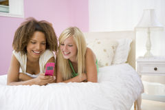 Adolescenti che si trovano sulla base per mezzo del cellulare Fotografie Stock Libere da Diritti