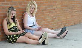 Adolescenti che texting con il mobile Immagine Stock
