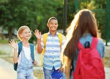 Adolescenti con gli zainhi che si incontrano nel parco Immagine Stock