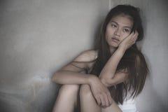 Adolescenti con i problemi, donna depressa triste che soffre a partire dalla vita familiare donne che si siedono nella stanza scu immagine stock