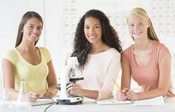 Adolescenti con il microscopio allo scrittorio nella classe di chimica Fotografia Stock