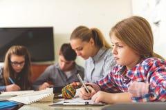 Adolescenti concentrati alla lezione affascinante Fotografia Stock
