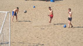 Adolescenti dei ragazzi che giocano a calcio sulla spiaggia archivi video