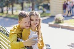 Adolescenti delle coppie su un banco fotografia stock