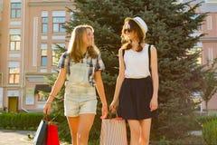 Adolescenti delle ragazze con i sacchetti della spesa sulla via della città Fotografia Stock