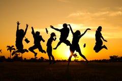 Adolescenti di salto della siluetta Fotografie Stock