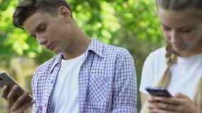Adolescenti dipendenti da Internet facendo uso degli smartphones, dipendenza della rete sociale video d archivio