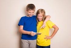 Adolescenti divertendosi con i telefoni cellulari Stile di vita e concetto moderni di tecnologia Bambini che guardano foto o vide immagine stock libera da diritti