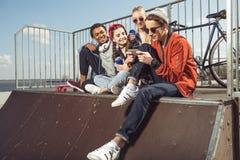 Adolescenti divertendosi con lo smartphone nel parco del pattino immagine stock