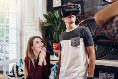Adolescenti emozionali che per mezzo della cuffia avricolare di VR per guardare i film 3D o per giocare andar in giroe a casa Immagine Stock