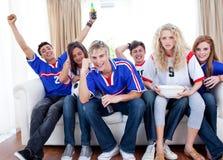 Adolescenti emozionanti che guardano una partita di gioco del calcio Fotografie Stock Libere da Diritti