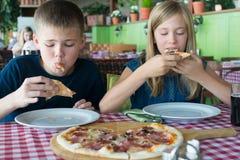 Adolescenti felici che mangiano pizza in un caffè Amici o fratelli germani divertendosi nel ristorante immagini stock libere da diritti