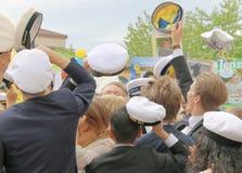 Adolescenti felici che sollevano la celebrazione del cappuccio di graduazione Fotografia Stock