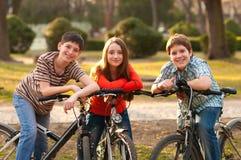 Adolescenti felici e ragazza che hanno divertimento sulle biciclette immagine stock