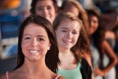 Adolescenti felici in una riga immagini stock