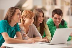 Adolescenti sorridenti che per mezzo di un computer portatile Fotografie Stock Libere da Diritti