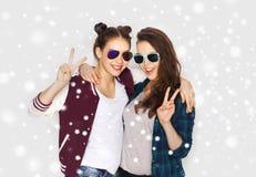 Adolescenti sorridenti in occhiali da sole che mostrano pace fotografia stock